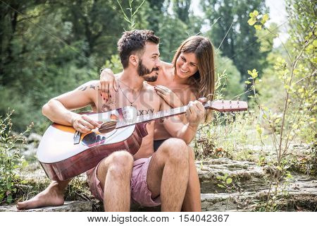 Couple of lovers playing guitar and singing - Boyfriend singing a romantic song for his girlfriend