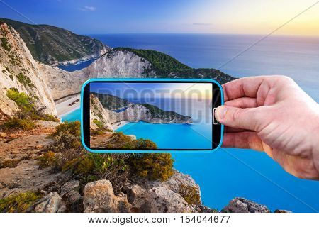Making photos by smartphone of Navagio beach in Greece