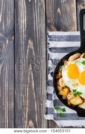 Hearty breakfast. Hash brown potatoes chicken onion parsley oregano and a fried egg in a frying pan on the old wooden background. Top view Selective focus.