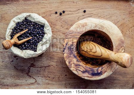 Closeup Black Pepper In Wooden Bowl With Mortar And Pestle On Shabby Teak Wood Table. Seasoning And