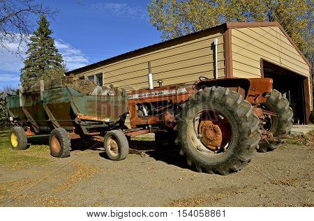 Clitherall, MINNESOTA, October 21, 2016:  The D-17 Allis Chalmers parked in front of a wagon bo full of firewood is an Allis Chalmersllis-Chalmers, a U.S. manufacturer of machinery for various industries includung agricultural equipment, construction, pow