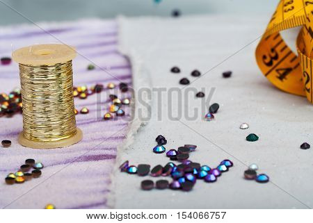 Sewing textile or cloth. Work table of a tailor. Measuring tape, reel of thread, and natural fabric. . Shallow depth of field. Focus reel of thread.