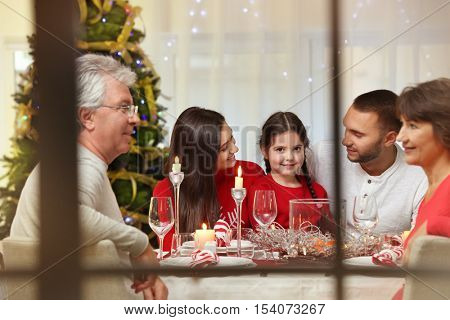 Happy family sitting at table served for Christmas dinner, view from window