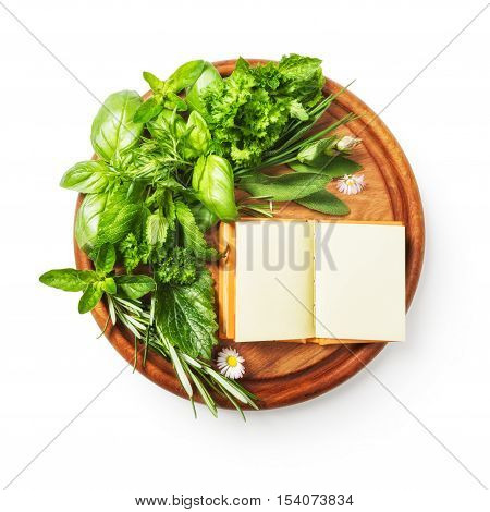 Herbs on cutting board. Fresh basil parsley sage peppermint rosemary bunch and recipe book. Single object isolated on white background clipping path included. Copy space top view flat lay
