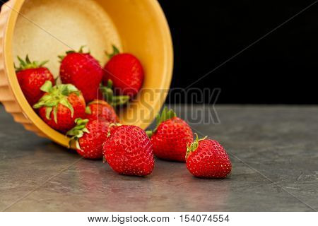 bowl of red juicy strawberries poured on its side isolated on a black background