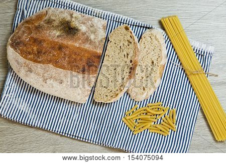 slices of ciabatta bread and spaghetti and noodles on a blue and white stripped cloth