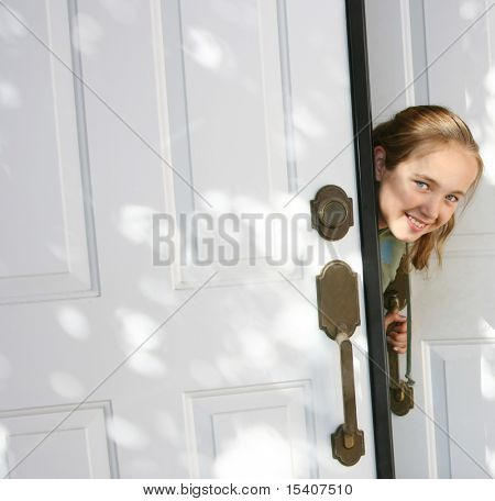 Smiling Young Pretty Girl Peeking Out Of Door
