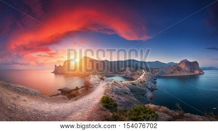 poster of Amazing summer landscape with mountains sea blue sky sun and beautiful colorful red clouds at sunset in Crimea. Sunset in mountains. Panoramic. Nature background. Vibrant landscape in twilight.