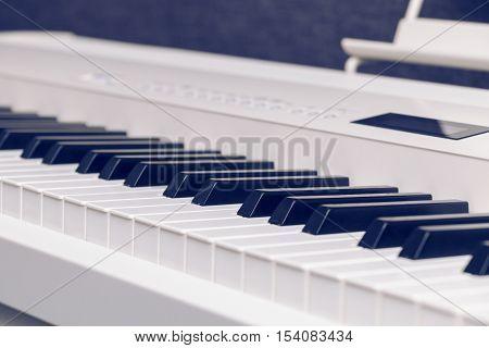 White ivory color digital piano keys closeup