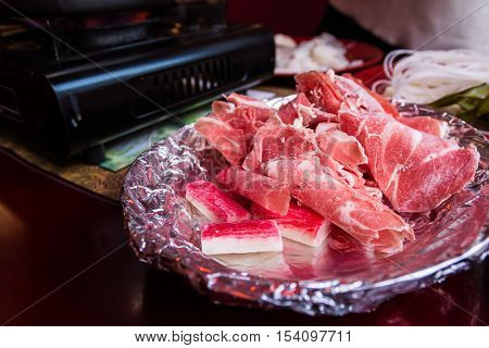 Aluminum Foil Plate Bowl Raw Meat Beef Pieces Collection Chinese Hot Pot Sharing Food Eating Restaurant Table Red White Detail Closeup