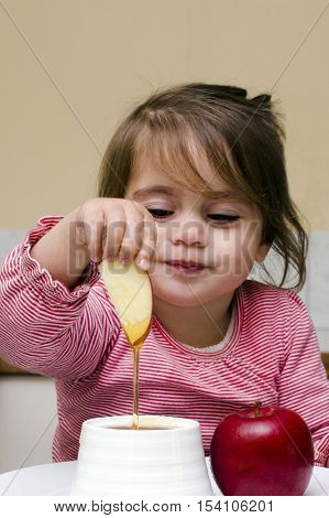 Jewish Girl Dipping Apple Slices Into Honey