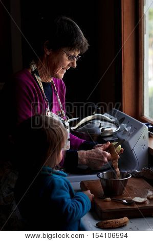 Grandmother And Grandchild Cooking In The Kitchen