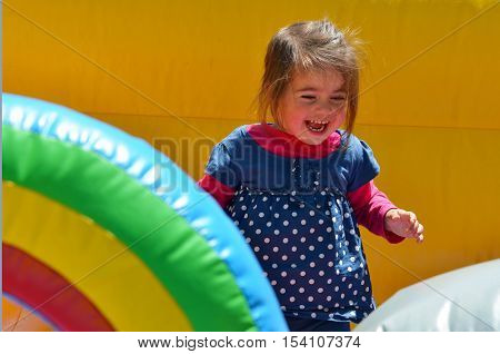 Little Girl Play In Inflatable Jumper Playground