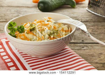 Coleslaw salad in bowl with silver fork on rustic table