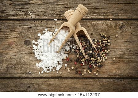 Heaps of coarse salt and mixed peppercorns on shovels, on rustic table, top view