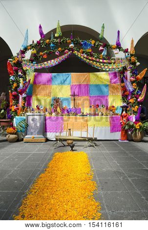 XALAPA, VERACRUZ, MEXICO - OCTOBER 28, 2016: Colorful Day of the dead offering altar, decorated wit cut paper, flowers, religion figures and food in Xalapa, Veracruz, Mexico