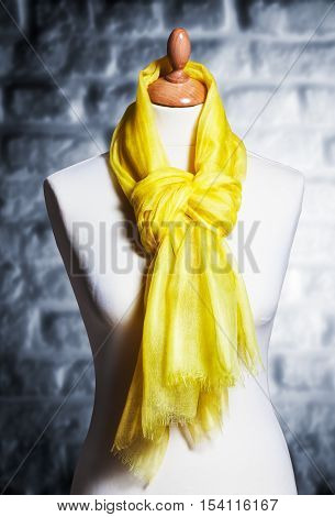 Mannequin with silk cloth. Knitted fashion yellow organza shawl on tailor bust. Single object with clipping path