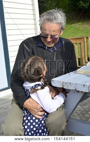 Great Granddad hug his great grandchild during home visit in his garden. Concept photo of senior citizen retirement pensioner relationship health and aging.