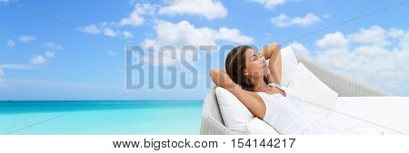 Asian woman relaxing lounging on white outdoor beach sofa daybed lounger on ocean background luxury vacation. Sleeping girl lying down comfortable enjoying the sun carefree happy. Home living.