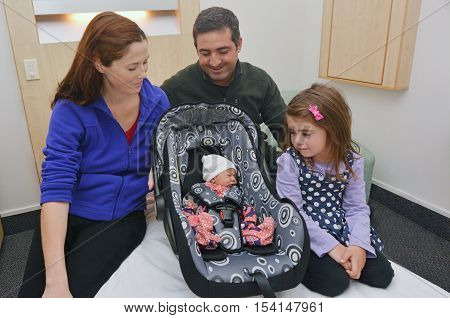 Healthy newborn baby in a car seat surrounded by his happy family: mother father and his sister after childbirth ready to go home. Concept photo of women healthy life style and health care. copy space