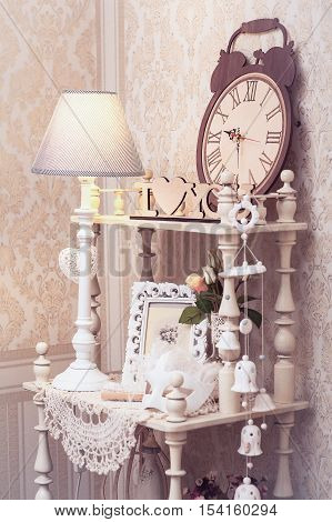 White Vintage Bookcase With Wooden Clock And Lamp