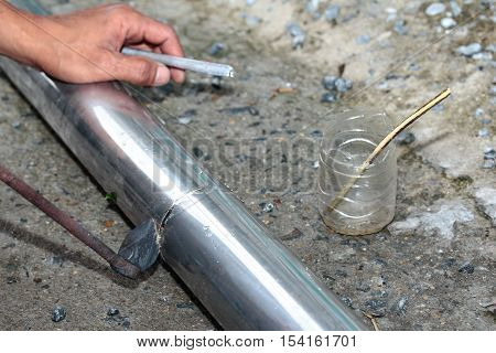 Aluminium gutter welding by using soldering copper with picnic gas:Technician is welding aluminium pipe by using soldering copper.