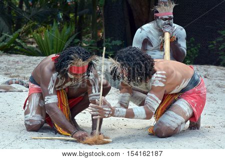 Group of Yugambeh Aboriginal warriors men demonstrate fire making craft during Aboriginal culture show in Queensland Australia.