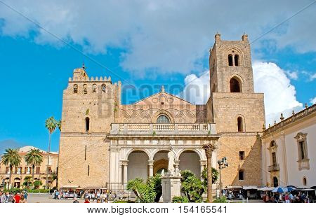MONREALE ITALY - OCTOBER 10 2016: The Cathedral of Assumption of Virgin Mary located in Square of Guglielmo II and surrounded by stalls of tourist market and cafes on October 10 in Monreale.