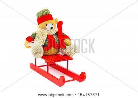 Dressed Christmas bear on wooden sledge isolated on white background