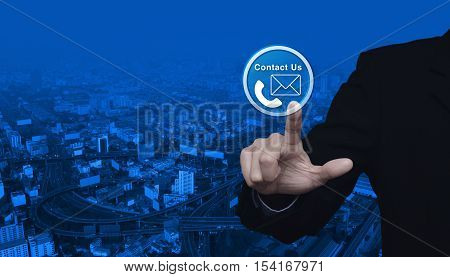 Businessman pressing telephone and mail icon button over city tower and street blue tone background Contact us concept