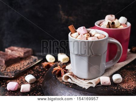 Hot chocolate with marshmallows and spices on grunge dark table. Selective focus, tasty holidays concept. Drink for fall and winter