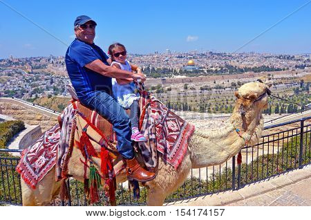Tourists (grandfather and his grandchild)m ride a camel against temple mount in the old city of Jerusalem Israel.