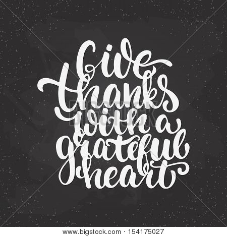 Give thanks with a grateful heart - Thanksgiving day lettering calligraphy phrase. Autumn greeting card isolated on the black chalkboard background.