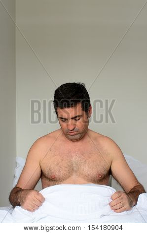 Upset Man In His Forties (40S) In Bed Looking Down At His Penis