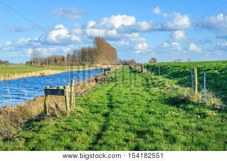 Bank of a small river between the water and dike on a sunny day in the winter season. On the banks are wooden posts of a fence. The blue sky is reflected in the water surface.
