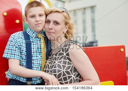Mother and son stand together head to head at playground in courtyard.