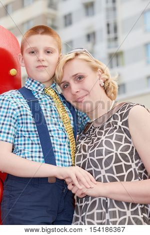 Mother and son stand together at playground in courtyard.