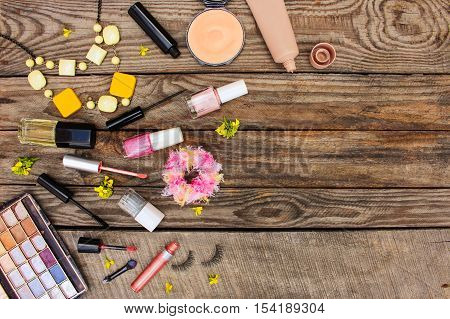 Cosmetics: mascara, beads, elastic hair band, false eyelashes, concealer, nail polish, perfume, eyeliner, powder, lip gloss, eye shadow and yellow flowers on wooden background. Top view
