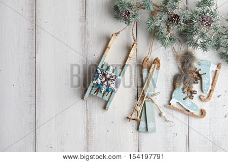 Wooden christmas decorations hanging over white fence on a fir tree