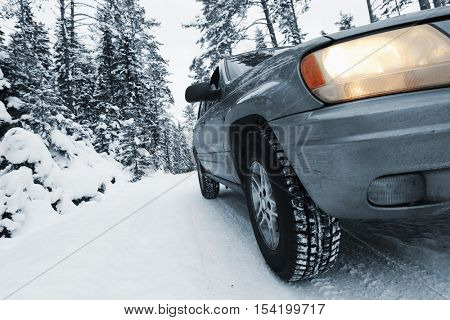 4x4 car, suv driving in snowy terrain and conditions, close ups on car but no trademarks