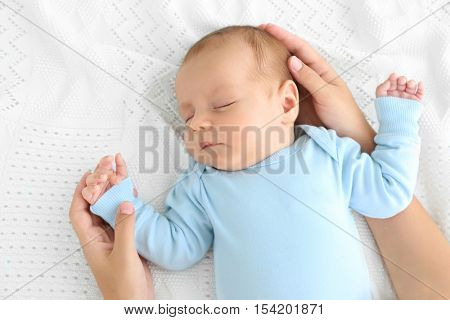 Mother hands touching cute sleeping baby, close up view
