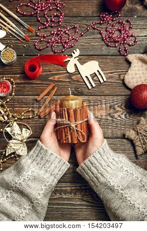 Girl in a bright sweater decorate a candle with using cinnamon