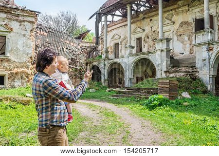 Pomoriany Castle a ruined castle in the village of Pomoriany Zolochiv District Lviv Oblast Ukraine. Man is showing his little son the ruins of once beautiful palace
