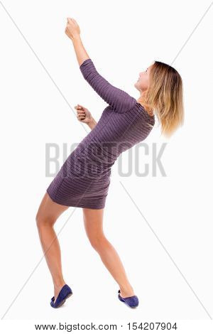 back view of standing girl pulling a rope from the top or cling to something. girl  watching.  backside view of person.  Isolated over white background. girl in  dress pulling a rope from the top.