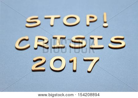Wooden text stop the crisis in 2017