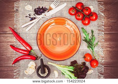 Fresh Tomatoes, Chili Pepper And Other Spices And Herbs Around Modern Orange Plate In The Center Of