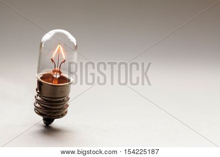Glowing light bulb, Retro style filament lamp macro view. Warm colors gradient background. Soft focus.