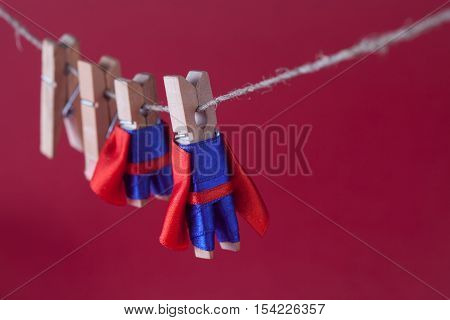 Super team leadership concept photo with clothespin superheroes in blue suit and red cape. Big small powerful heroes hanging clothesline. Pink background. macro view
