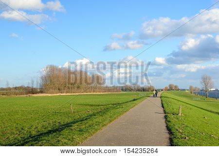 Bike and walking path over an embankment along a wide river in the Netherlands. It's a sunny day in the winter season and in the background an elderly couple is strolling together.