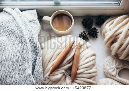 Stack of cozy knitted sweaters, thick yarn and wooden needles on window sill, top view. Morning coffee in lazy winter weekend.